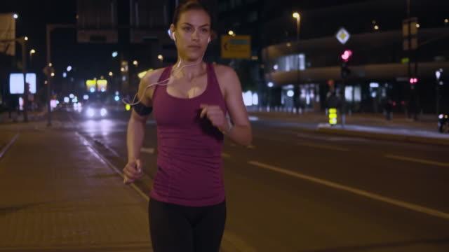 slo mo ts kadın bir akşam şehrin içinden çalıştırmak - kulaklık seti ses ekipmanı stok videoları ve detay görüntü çekimi