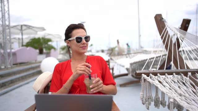 Woman on beach hoiday working on laptop Woman at beach cafe is using laptop minority groups stock videos & royalty-free footage