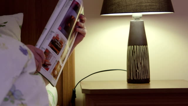 Woman on bed in bedroom finished reading magazine turns off the lamp video