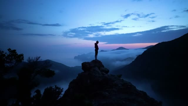 Woman on cliff above coastline of Corsica with remote beach and covered in fog after sunset Corsica coastline and beach on colorful sunset cliffs stock videos & royalty-free footage