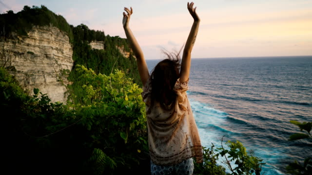woman on cliff with view on  ocean in bali - индонезия стоковые видео и кадры b-roll
