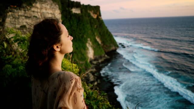 懸崖上的女人在巴厘島的海洋觀 - 懸崖 個影片檔及 b 捲影像