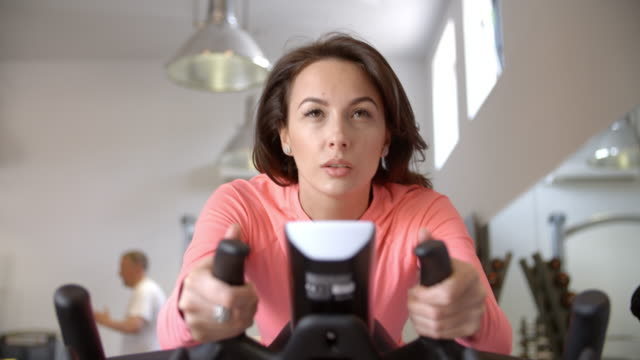 Woman on exercise bike in exercising class at a gym, close up Woman on exercise bike in exercising class at a gym, close up exercise bike stock videos & royalty-free footage