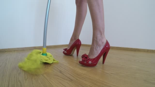 woman on high heels washes the parquet floor with the yellow mop - scarpe video stock e b–roll