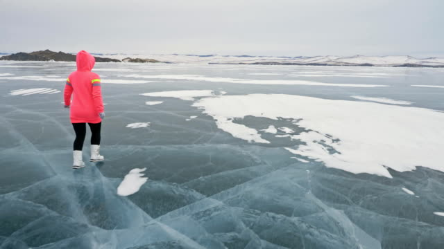 Woman on ice in winter is do sport in athletic race walking. Girl is training in winter on ice. Sports nordic power walking athlete prepares for sport competition exposure.