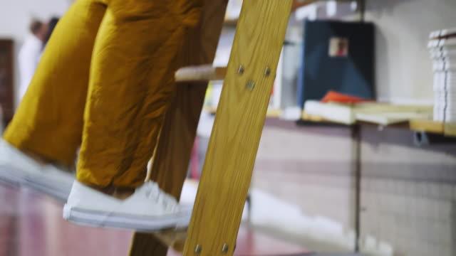 stockvideo's en b-roll-footage met vrouw op ladder zoeken boeken in de buurt boekenkasten in de bibliotheek - ladder