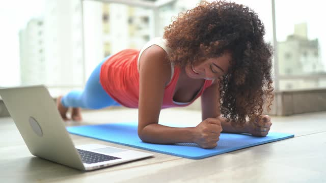 Woman on plank position doing exercise at home
