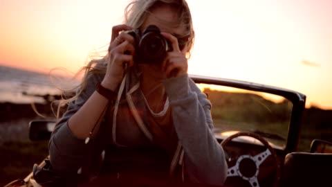 vídeos de stock e filmes b-roll de woman on road trip sitting in convertible and taking photos - fotografia imagem
