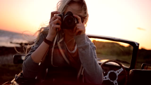 vídeos de stock e filmes b-roll de woman on road trip sitting in convertible and taking photos - passeio