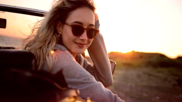 frau auf roadtrip mit cabrio entspannend bei sonnenuntergang - sonnenbrille stock-videos und b-roll-filmmaterial