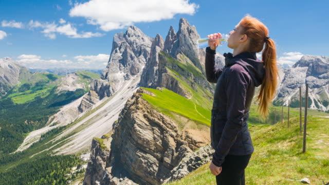 Frau auf Seceda Berg erkunden Dolomiten, feuchtigkeitsspendende aus einer wiederverwendbare Wasserflasche – Video