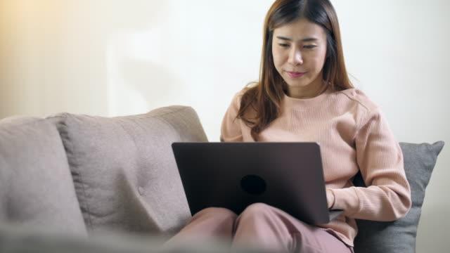 kvinna på soffan hemma med hjälp av bärbar dator - working from home bildbanksvideor och videomaterial från bakom kulisserna