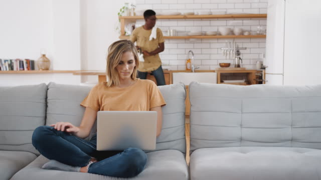 Woman On Sofa At Home Using Laptop Computer With Man In Kitchen Behind
