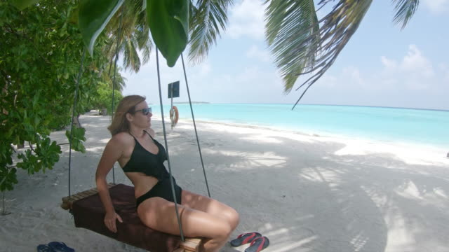 MS Woman on swing on idyllic,tropical ocean beach,Maldives MS Woman on swing on idyllic,tropical ocean beach,Maldives. Zoom In,Real Time. one mid adult woman only stock videos & royalty-free footage