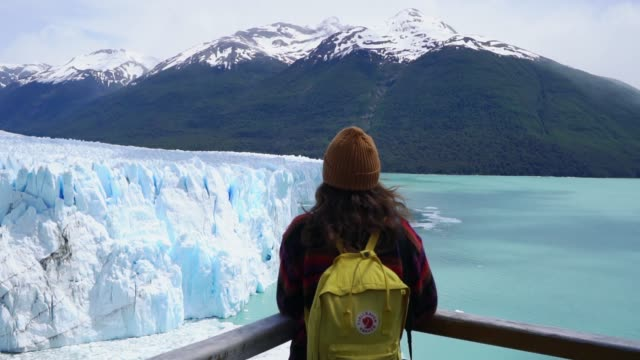 Woman on the background of scenic view of Perito Moreno Glacier in Patagonia