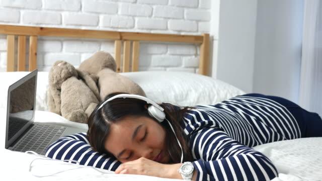dizüstü bilgisayar ile müzik dinlemek yatakta kadın - kulaklık seti ses ekipmanı stok videoları ve detay görüntü çekimi