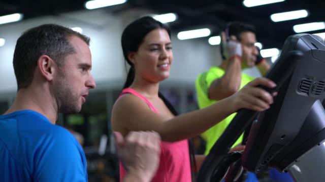 frau auf dem crosstrainer und ihr personal trainer neben ihr - lehrerin stock-videos und b-roll-filmmaterial
