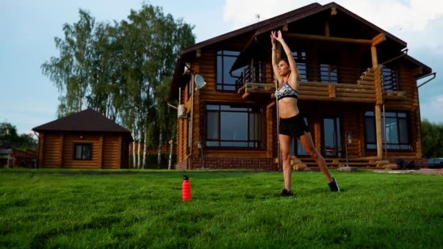 Woman on the grass doing yoga on the background of a beautiful house. The concept of a healthy lifestyle Woman on the grass doing yoga on the background of a beautiful house. The concept of a healthy lifestyle. bodyweight training stock videos & royalty-free footage