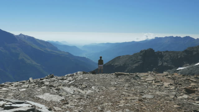 Woman on the mountain top on the Italian French Alps, slow motion video