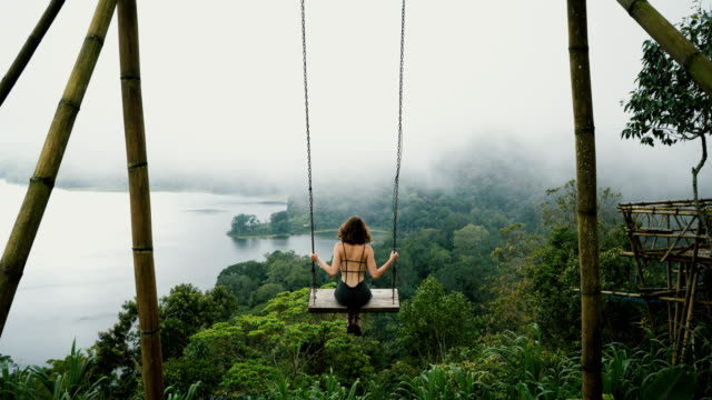 Woman on the swing over the jungles and lake  in Bali Young Caucasian woman  on the swing with view of lake in Bali outdoor play equipment stock videos & royalty-free footage