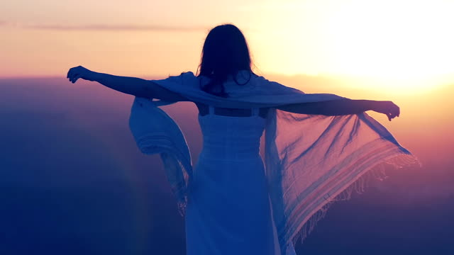 woman on the top of a mountain is viewing  plain in front of her at the sunset video