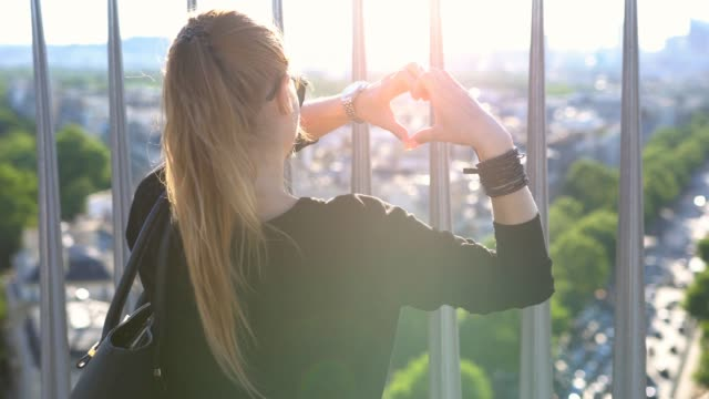 kvinna på toppen av triumfbågen som bildar ett hjärta form med händerna - fransk kultur bildbanksvideor och videomaterial från bakom kulisserna
