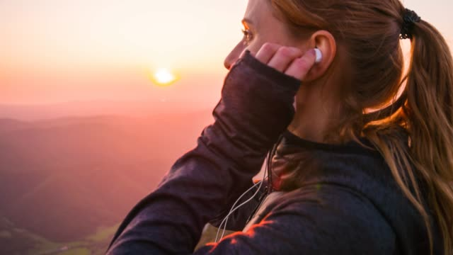 Woman on top of mountain looking at sunset, inserting earphones Young woman on top of the mountain inserting earphones in her ears, listening to music on her smartphone and admiring the sunset headphones stock videos & royalty-free footage