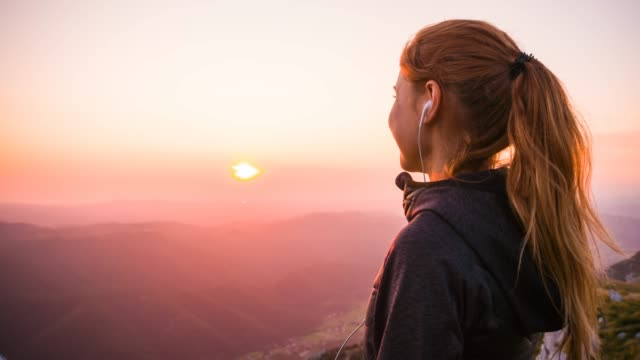 woman on top of the mountain looking at sunrise - in cima video stock e b–roll