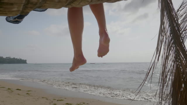 A woman on vacation relaxes on a palm tree at the sea on a desert island and plays by moving her legs.