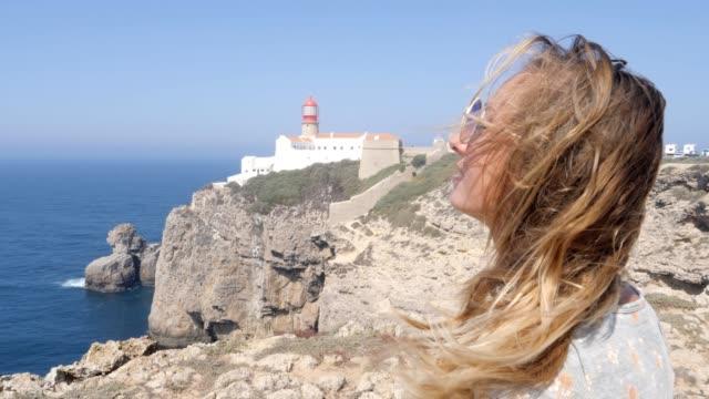Woman on vacation, tourist looking at lighthouse above cliffs in Portugal.