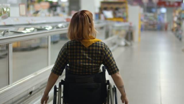 vídeos de stock, filmes e b-roll de mulher na cadeira de rodas, fazer comida, fazer compras no supermercado - acessibilidade