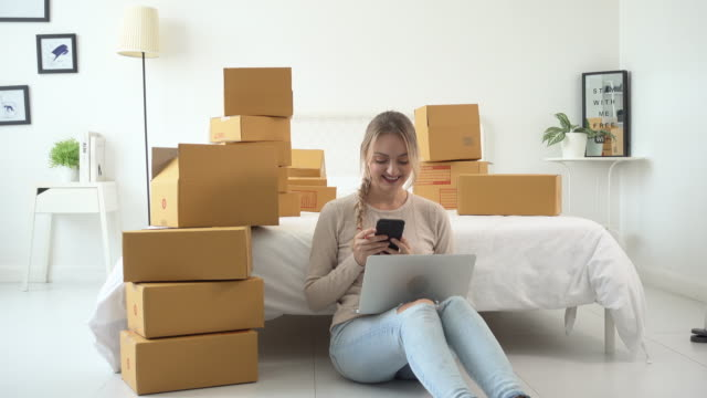 Woman online sale with her Smart phone and courier parcel box at home office at home