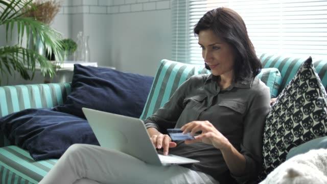 女性オンライン ショッピングのラップトップで家庭で - 通販点の映像素材/bロール