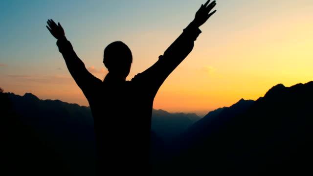 Woman open arms to mountain