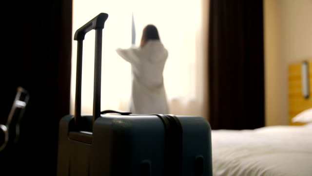 woman open curtain in hotel room with luggage