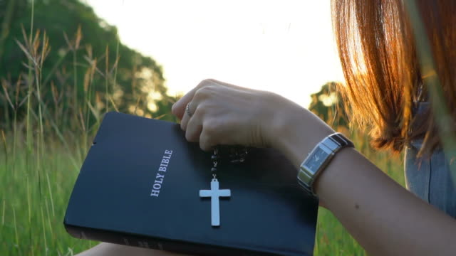 vídeos de stock e filmes b-roll de woman open the bible and cross hanging over - crucifixo