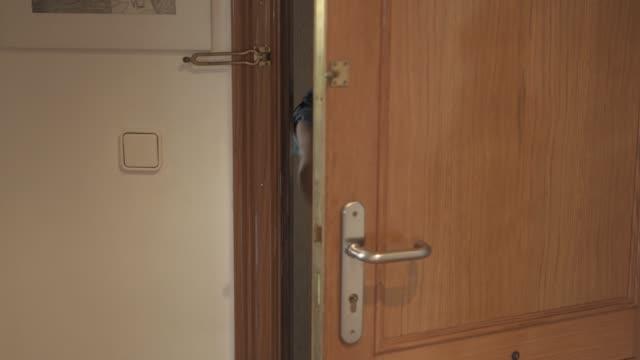 vidéos et rushes de femme ouvrent la porte laissant l'appartement - porte entrée