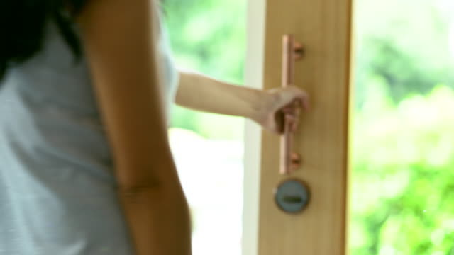 woman open the glass door and going outside. - odejście filmów i materiałów b-roll