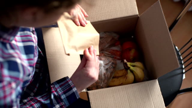 woman opening a Food delivery box at home video