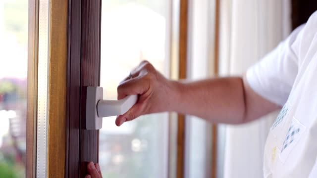 Woman opening and closing the door Close up video of senior woman hands opening and closing terrace door in the house. handle stock videos & royalty-free footage