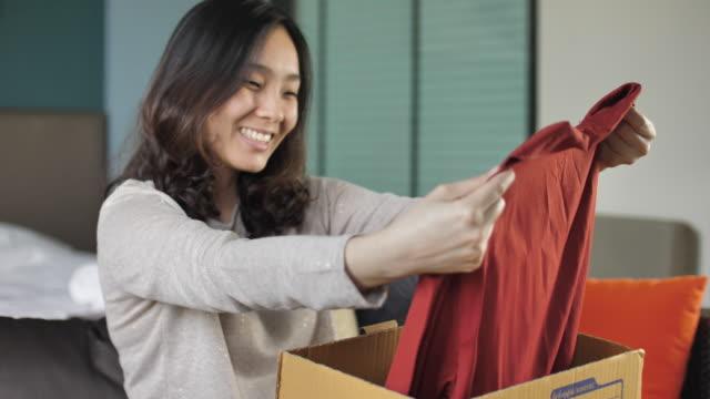 vídeos de stock, filmes e b-roll de mulher, abrindo a caixa de papelão em casa - comércio eletrônico