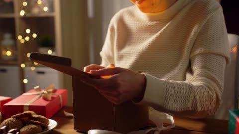 vidéos et rushes de femme ouvrant le cadeau de noel à la maison - cadeau