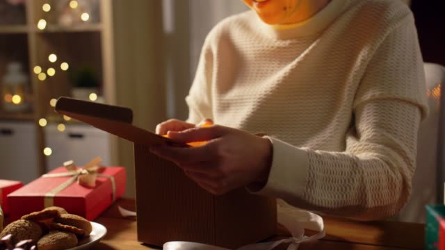 kvinna öppnar julklapp hemma - christmas presents bildbanksvideor och videomaterial från bakom kulisserna