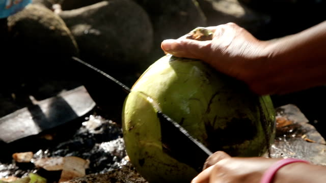 woman opening coconut with big knife Woman on a public market opens coconuts with machetes.Asian market coconut stock videos & royalty-free footage