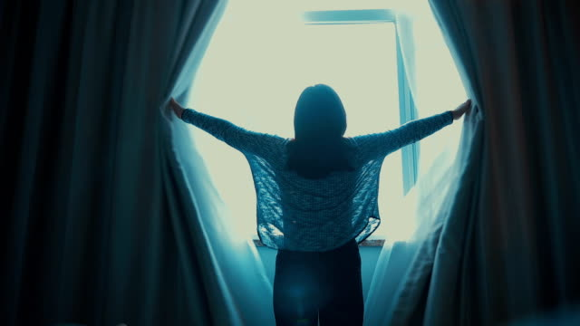 Woman opening curtains in the room video