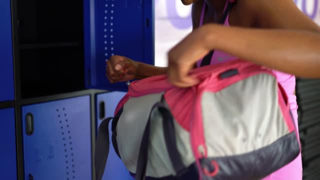 Woman opening her bag at the locker gym Beautiful woman opening her bag at the locker gym smiling locker stock videos & royalty-free footage