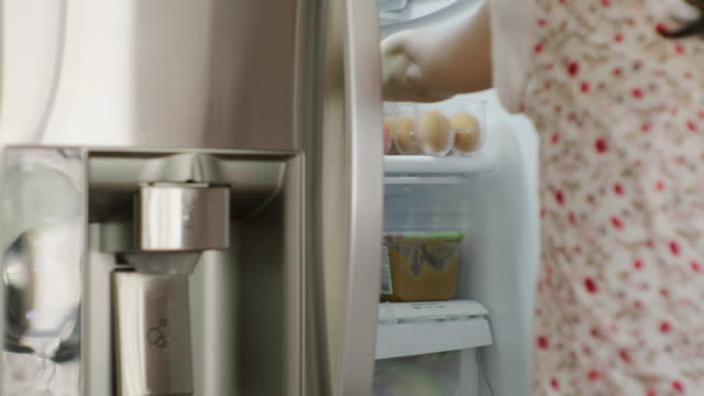 Woman Opening Home Refrigerator A women taking food from a home kitchen refrigerator. fridge stock videos & royalty-free footage