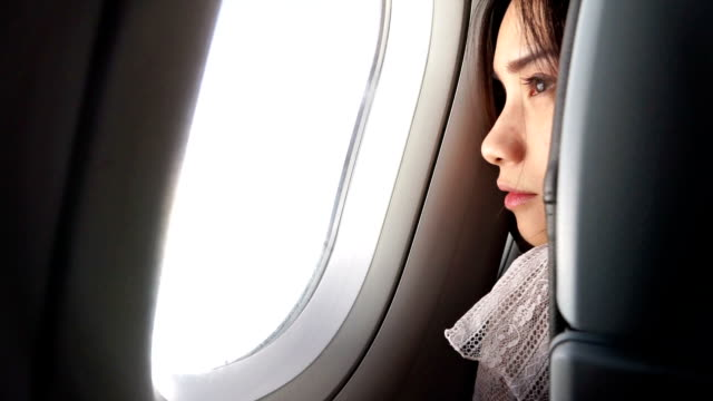 Woman opening the blind and Looking Outside of Airplane Window video