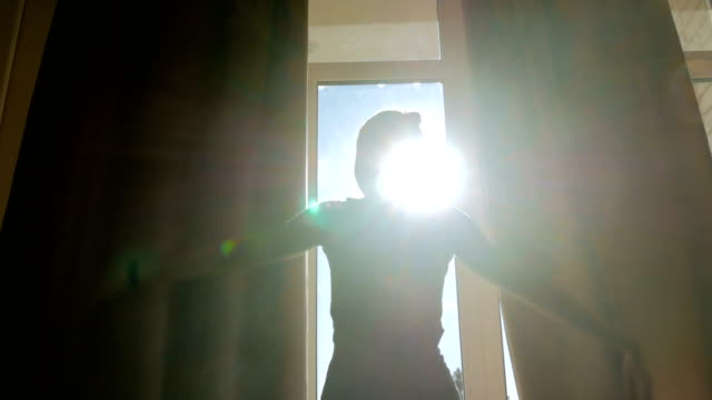 Woman opening window curtains Woman silhouette opening curtains and looking out of window in hotel room at morning silhouette people stock videos & royalty-free footage