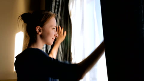 Woman opening window curtains Happy woman opening curtains and looking out of window in cabin of cruise ship at morning morning stock videos & royalty-free footage